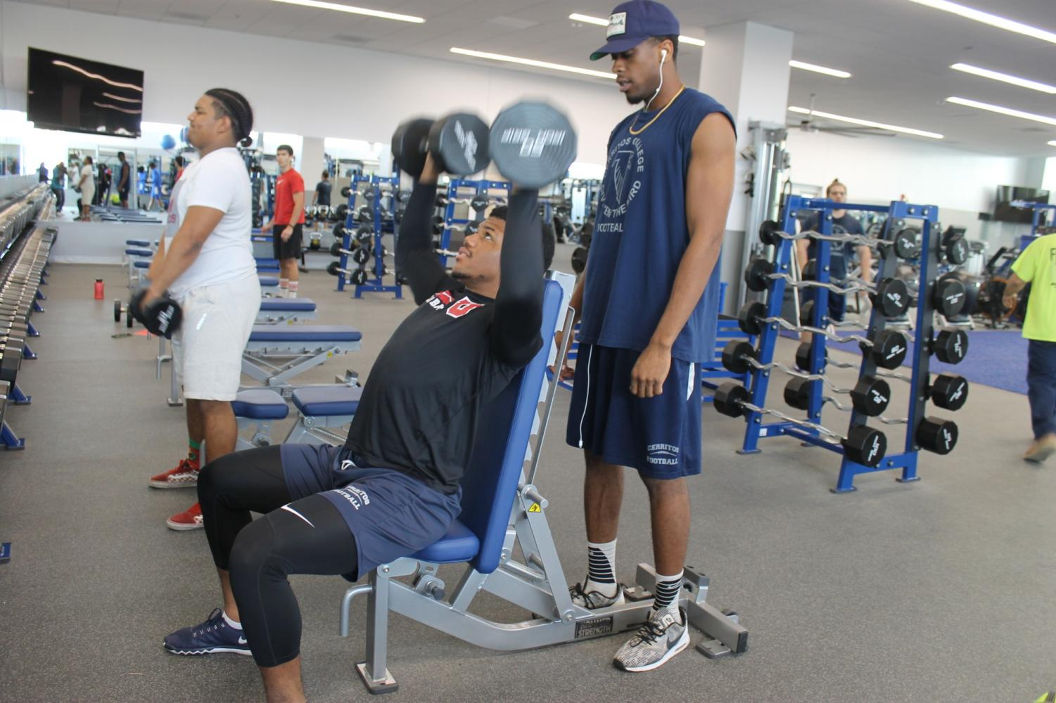 Cerritos College running back Carl Odom gets a shoulder press lift in the new weight room facility.