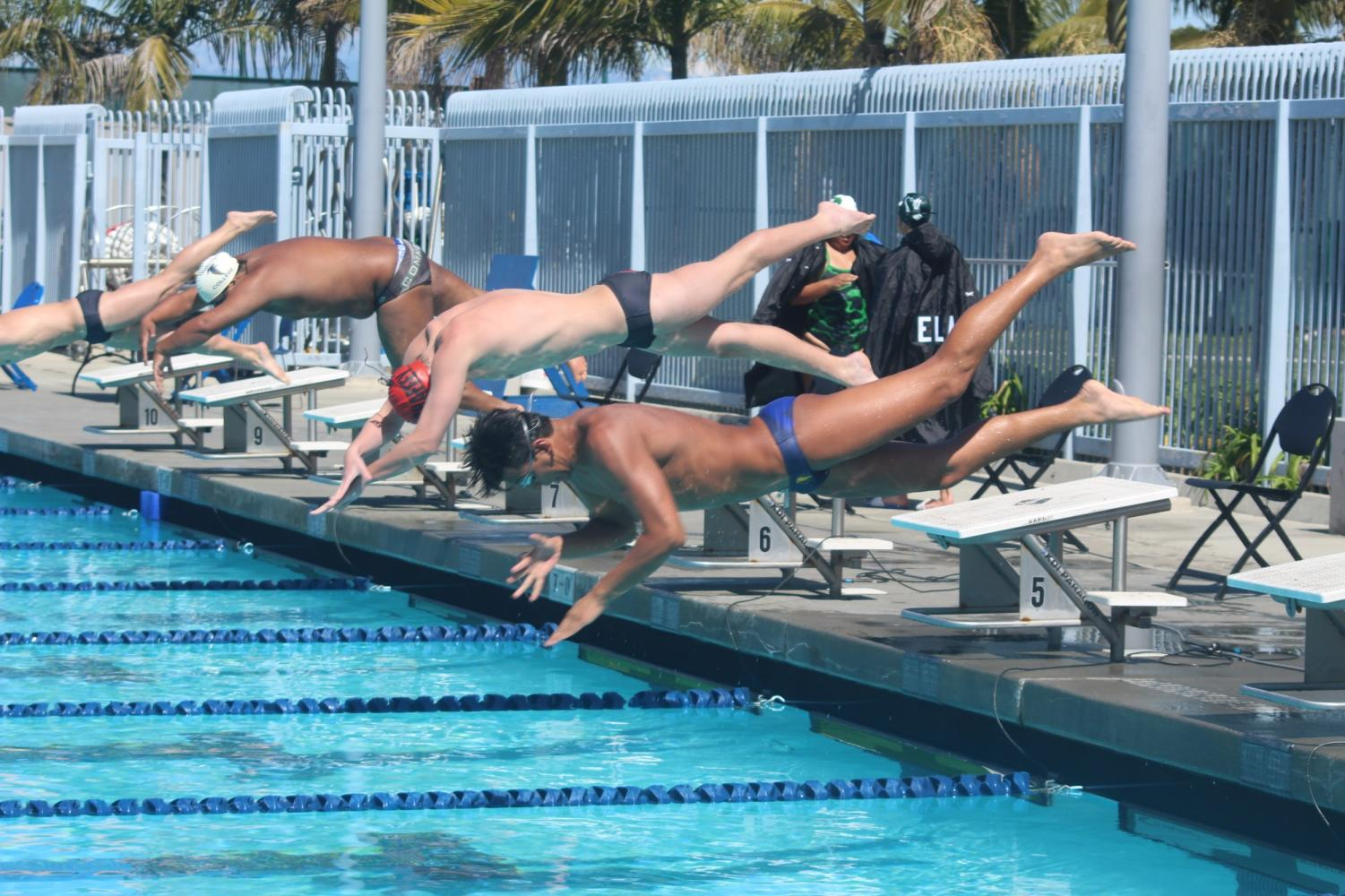Men falcons stretch off the block at the start of the 200 Butterfly. The Falcons will later finish in the top 3. Photo credit: Christopher Martinez