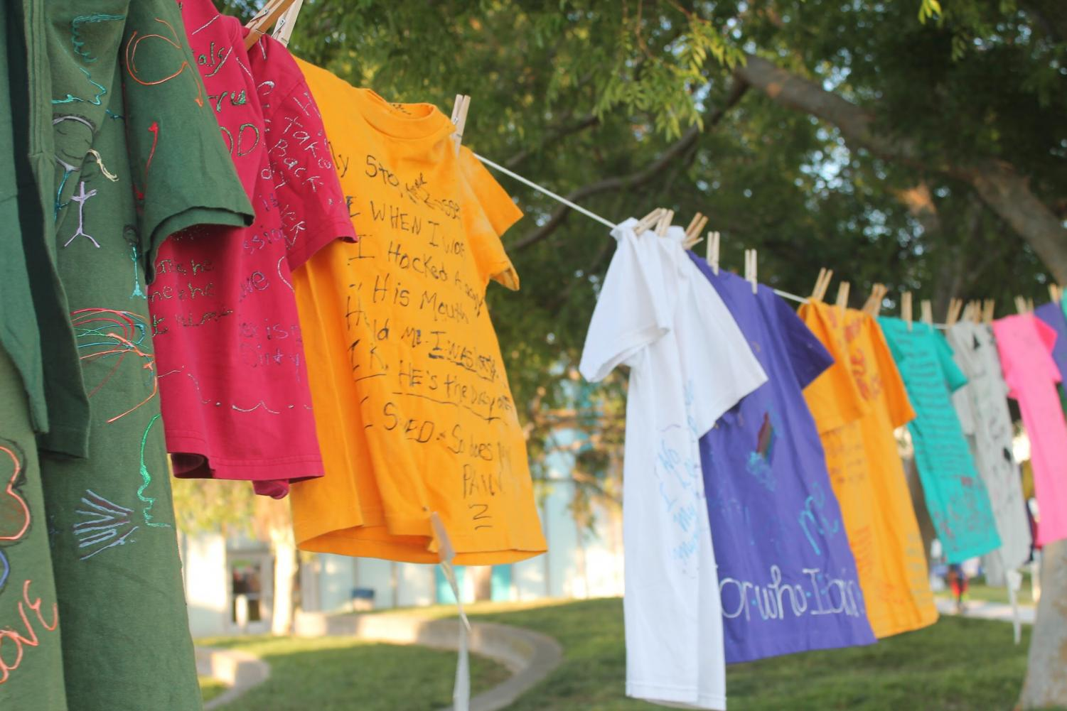 The Clothesline Project was displayed behind the resource booths at Take Back the Night. This idea consisted of shirts given by sexual assault survivors, with their stories written across them.