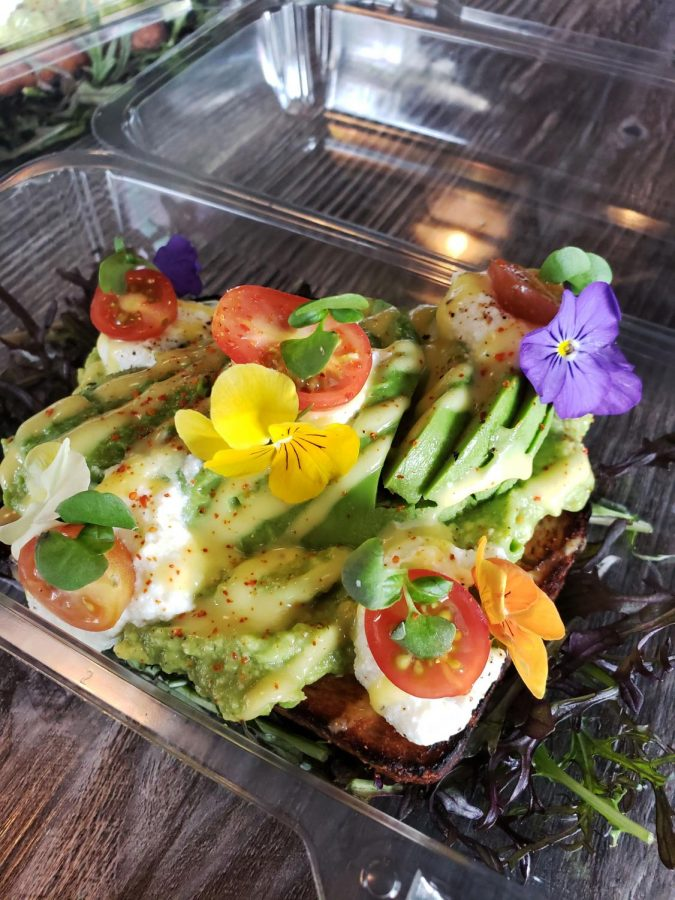Delicious avocado toast decorated with lovely delicate viola flowers
