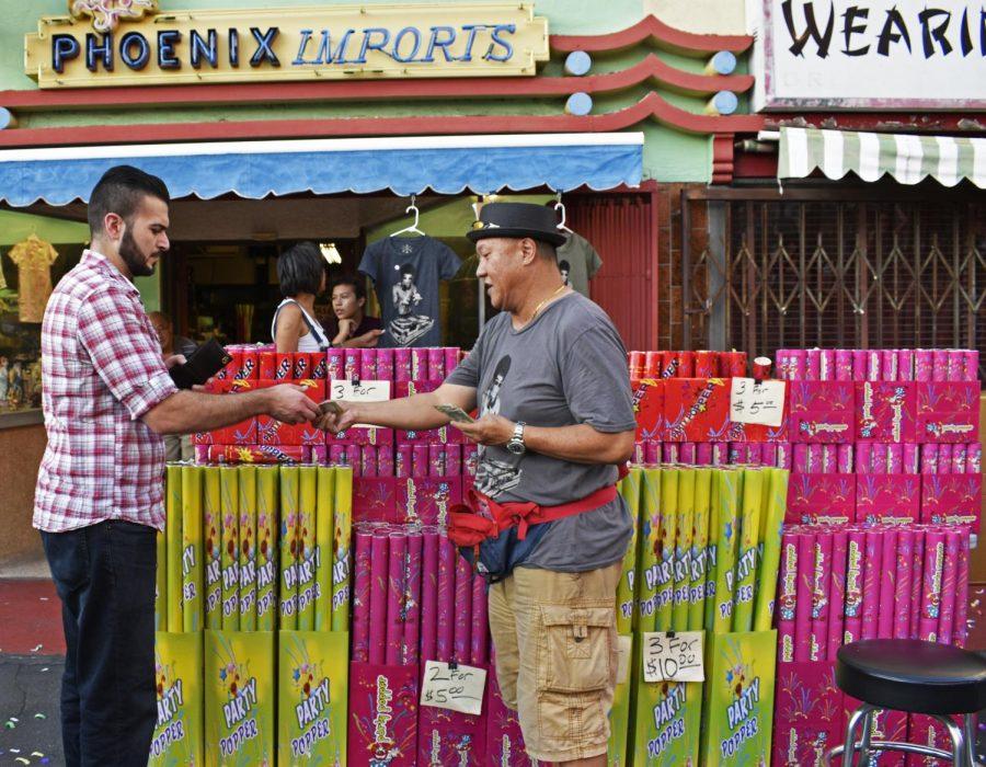 Glen SooHoo of Phoenix Imports sells confetti poppers. LA Chinatown Mid-Autumn Moon Festival on Sept. 15, 2019.