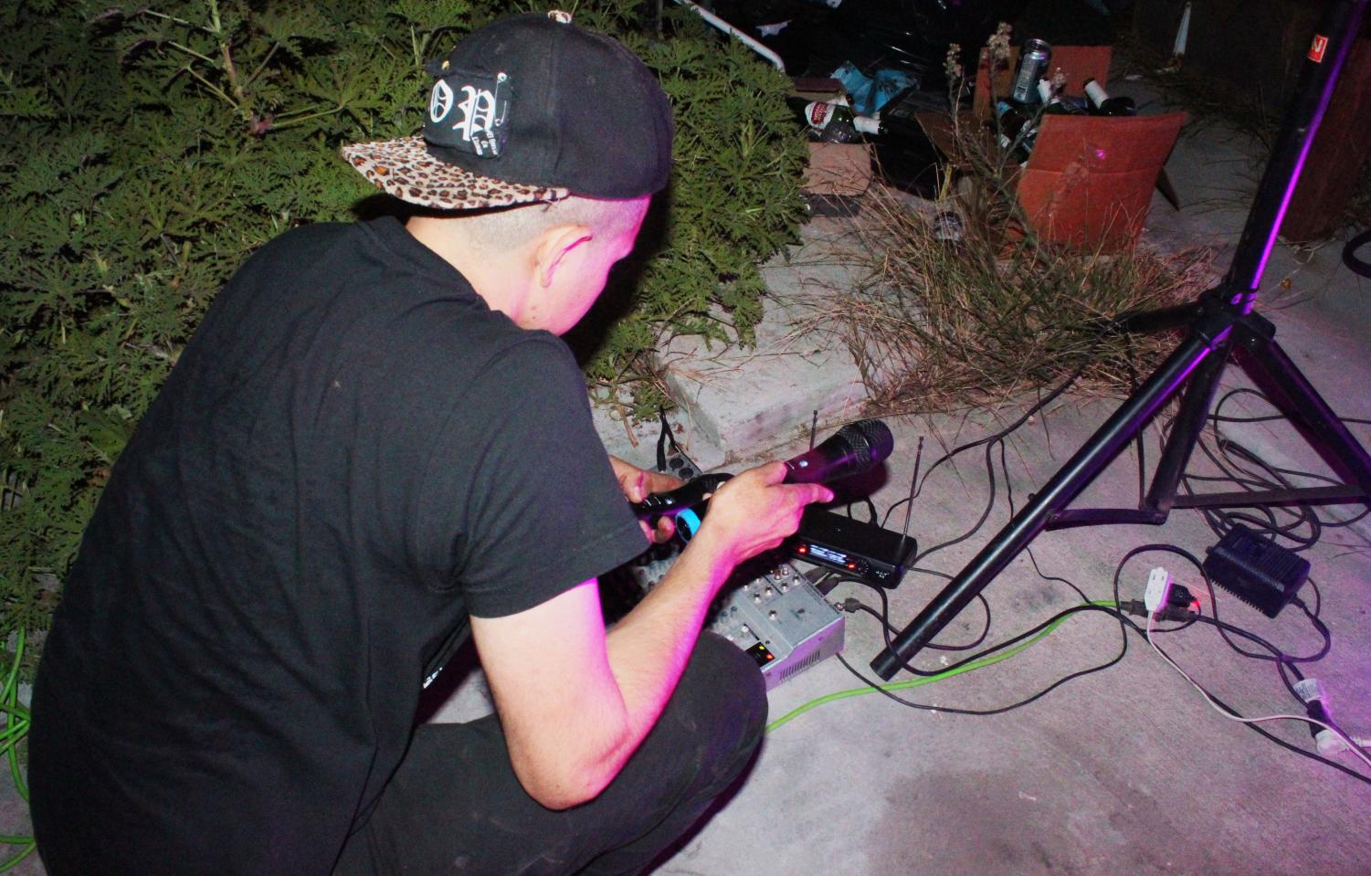 Sabino Sanchez, 29, sets up his microphones into his sound board before the first band performs