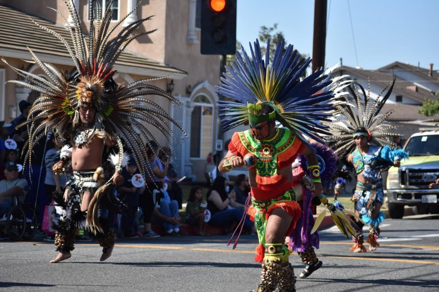 Danza Azteca Huehueteotl perform on Norwalk Boulevard. They were dressed in Aztec attire and many were barefoot on the hot street floor.