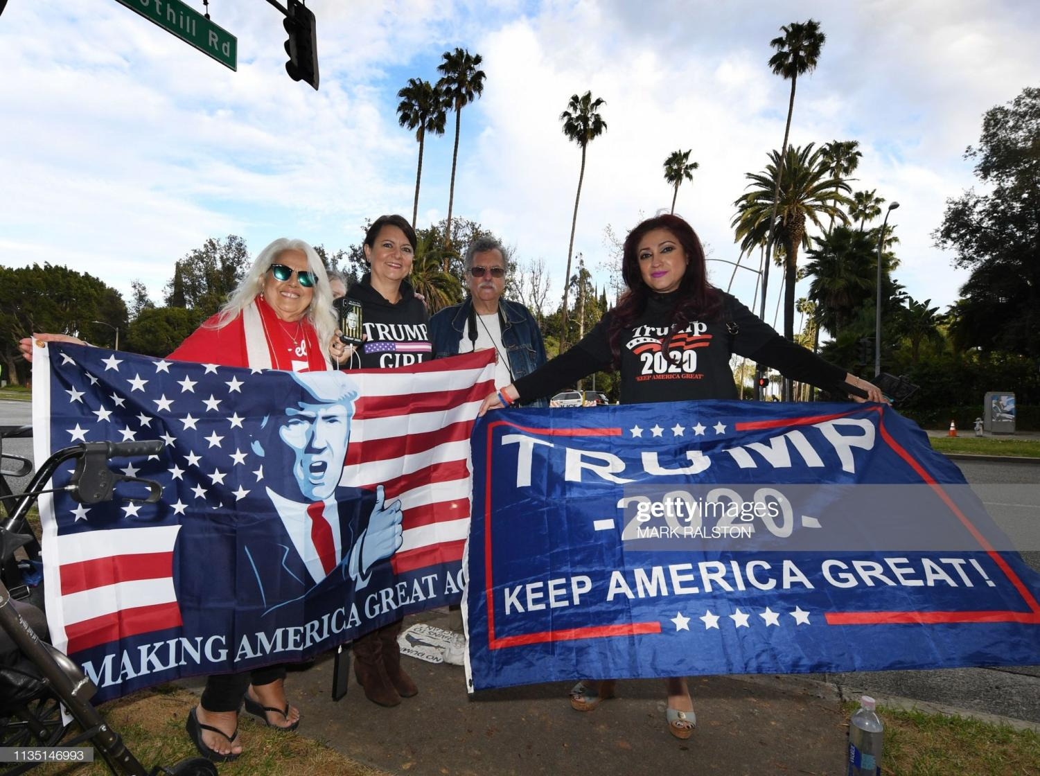 TOPSHOT - Trump supporters pose for photos on Sunset Blvd as the US president attends a fundraiser nearby, in Beverly Hills, California, on April 5, 2019. - US President Donald Trump visited the Mexican border on April 5 to deliver a message to would-be illegal immigrants and asylum seekers: don't bother coming.