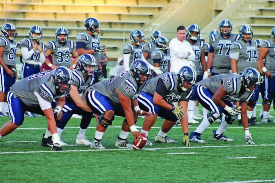 Quarterback prepares with the offensive line in front before the ball is snapped. The Falcons run drills before the homecoming game on Nov. 2, 2019.