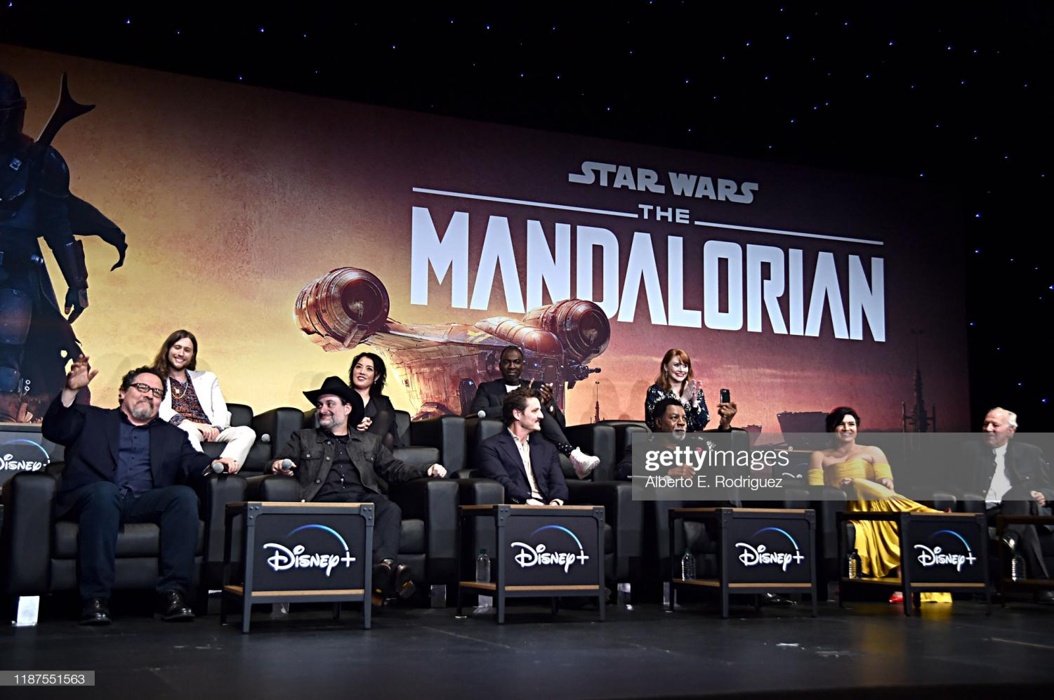 HOLLYWOOD, CALIFORNIA - NOVEMBER 13: (L-R) Executive Producer Jon Favreau, Composer Ludwig Göransson, Executive Producer/Director Dave Filoni, Director Deborah Chow, Pedro Pascal, Rick Famuyiwa, Carl Weathers, Director Bryce Dallas Howard, Gina Carano and Werner Herzog speak onstage at the premiere of Lucasfilm's first-ever, live-action series,