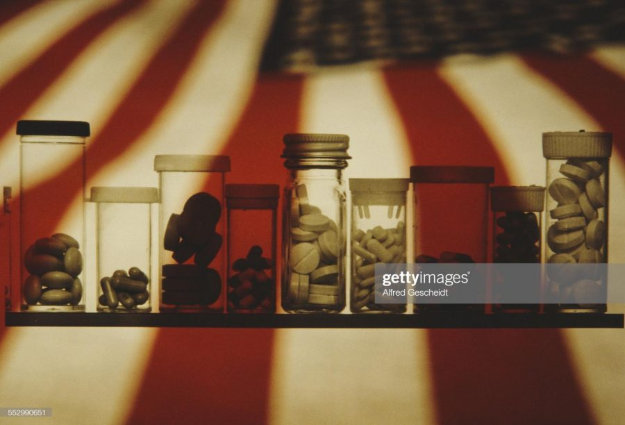 An assortment of pill bottles set against the backdrop of the American flag, 1982.