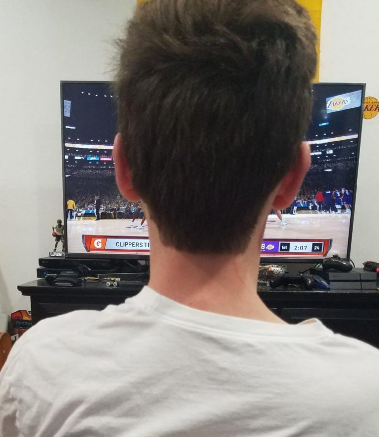 Andrew Ortiz watches NBA palyers playing NBA2K20 on tv as the leauge is still shutdown.
