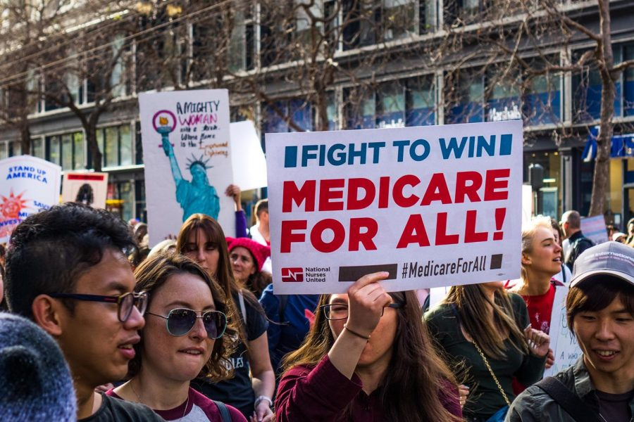 A+woman+at+the+Womens+March+holds+Medicare+for+all+sign+while+marching+on+Market+street+in+downtown+San+Francisco.+%28Dreamstime%2FTNS%29