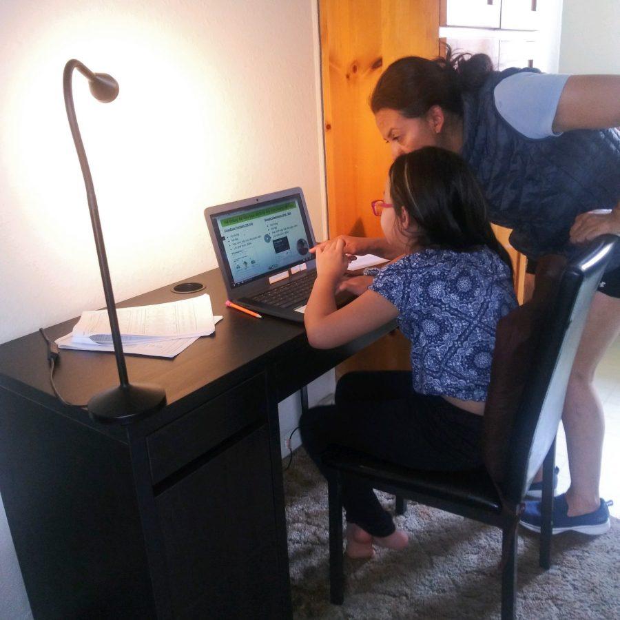 Amada M. Torres helping her daughter Maria with online school work.