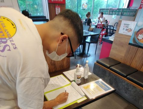 Dining guest fills out mandatory customer log with their contact information before entering a local restaurant. Restaurants and bars are required to keep a log of all their visitors for contact tracing purposes. Photo credit: Mirella Vargas
