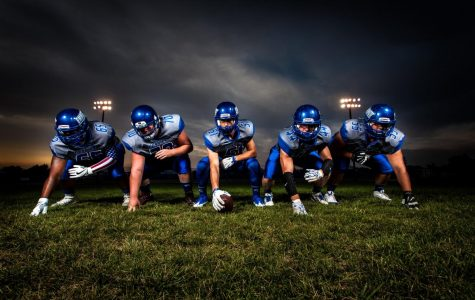 Football players in blue jersey-lined under Grey white cloudy sky during sunset. Players are ready for game time. Photo credit: Binyamin Mellish/Pexels.com