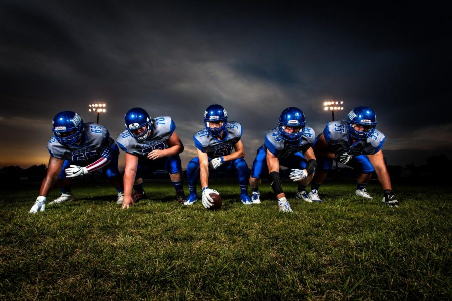 Football+players+in+blue+jersey-lined+under+Grey+white+cloudy+sky+during+sunset.+Players+are+ready+for+game+time.+Photo+credit%3A+Binyamin+Mellish%2FPexels.com