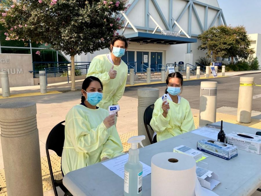 Second-year nursing students Julia Castaneda (left) Alexander Kim and Ester Perez take temperatures of students before they enter the study hall. Photo credit: Vincent Medina