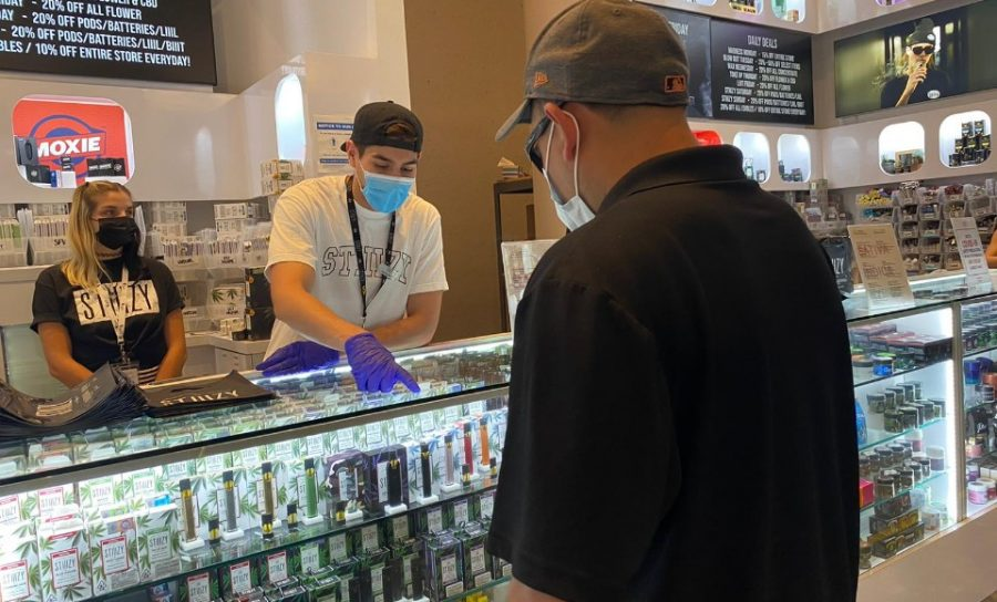 Sales employee at popular cannabis retailer assisting a customer. All employees are required to wear a face mask and gloves during their shift. Photo credit: Mirella Vargas
