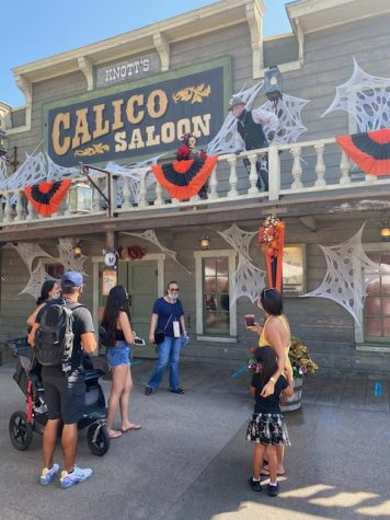 Characters engage with park patrons who enjoy friendly Halloween banter. Several buildings are decorated with various Halloween Themes.
