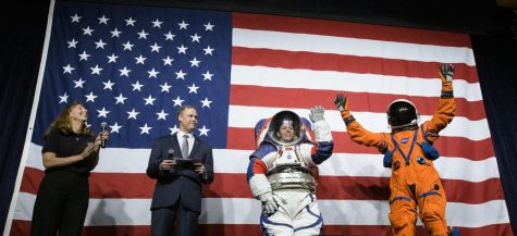 Amy Ross, a spacesuit engineer at NASA's Johnson Space Center, left, and NASA Administrator Jim Bridenstine, second from left, watch as Kristine Davis, a spacesuit engineer at NASA's Johnson Space Center, wearing a ground prototype of NASA's new Exploration Extravehicular Mobility Unit (xEMU), and Dustin Gohmert, Orion Crew Survival Systems Project Manager at NASA's Johnson Space Center, wearing the Orion Crew Survival System suit, right, wave after being introduced by the administrator, Tuesday, Oct. 15, 2019 at NASA Headquarters in Washington. The xEMU suit improves on the suits previous worn on the Moon during the Apollo era and those currently in use for spacewalks outside the International Space Station and will be worn by first woman and next man as they explore the Moon as part of the agency's Artemis program. The Orion suit is designed for a custom fit and incorporates safety technology and mobility features that will help protect astronauts on launch day, in emergency situations, high-risk parts of missions near the Moon, and during the high-speed return to Earth. Photo credit: NASA/Joel Kowsky