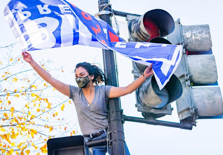 A woman climbs a street light on Pennsylvania Ave. Washington D.C. in celebration for the Biden win. His victory was called by major news outlets on Nov. 7.