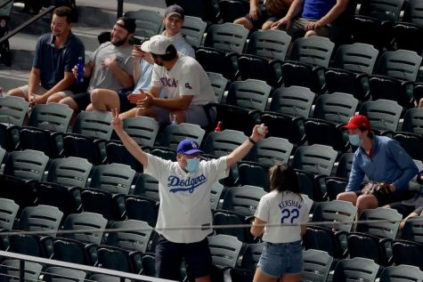 A Los Angeles Dodgers fan celebrates catching a foul ball during game one of the National League Championship Series between the Dodgers and the Atlanta Braves. Photo credit: Ron Jenkins