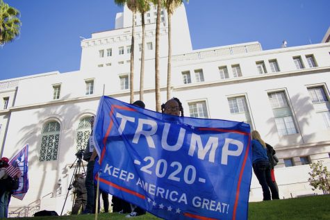 """San Jacinto Councilmember Bryan Hawkins' daughter, Noria, waves a Trump flag at the """"Stop the Steal"""" rally on Jan. 6. Her father spoke to a crowd of over 100 maskless protesters at Los Angeles city hall to spread conspiracy theories about why Democrats won the election."""