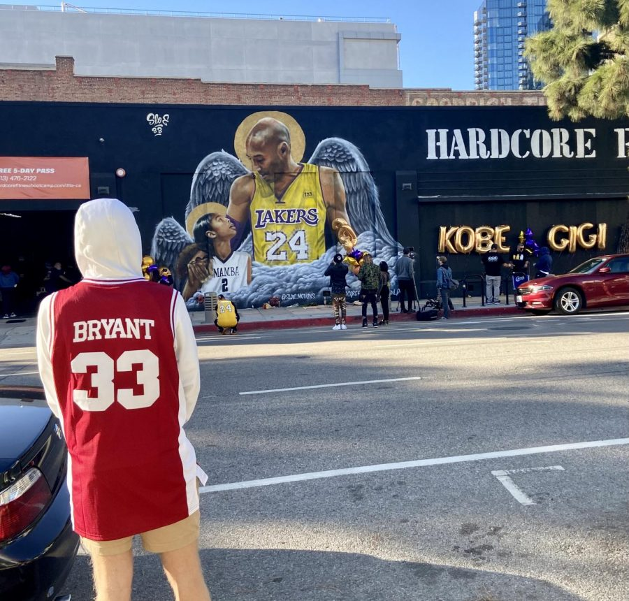 USC student Jett Sacks visits Kobe Bryant and Gianna Bryant mural on Pico Blvd, honoring the one year anniversary of their deaths. Sacks is wearing Bryant's high school jersey in his honor on Jan. 26, 2021 Photo credit: Emily Melgar