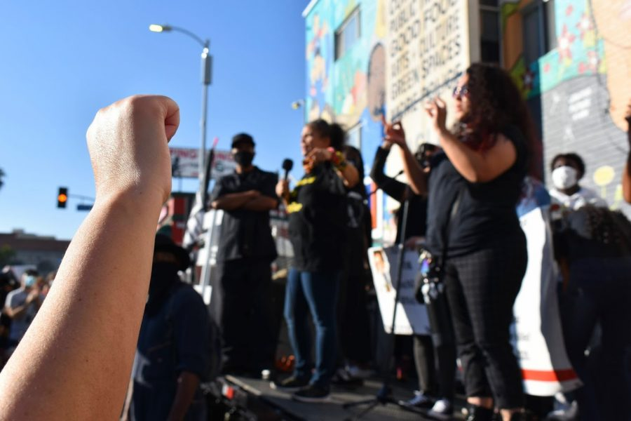 Black Lives Matter supporters raise their fists as BLM LA co-founder Malina Abdula speaks at a rally on Feb. 24, 2021. BLM plans to protest outside the ACLU every Wednesday until their demands are met.
