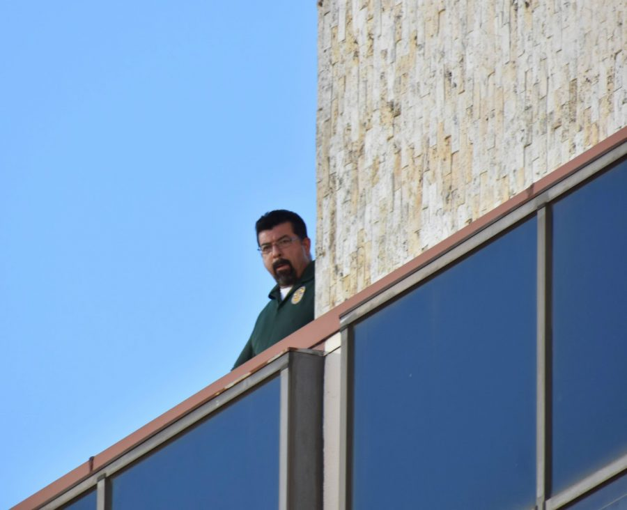 An officer watches the Black Lives Matter rally from the roof of the LA Police Protection League Headquarters on Feb. 24, 2021. Malina Abdula referred to the league as the side of injustice.