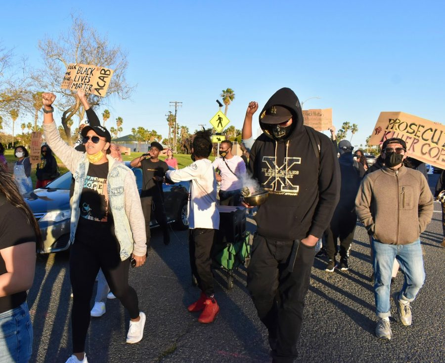 Activists march to honor African-American's role in American history during a Black History Month celebration on Feb. 20, 2021. They marched through Marina Park in Long Beach.