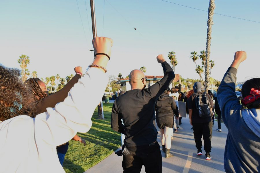 Marchers hold their fists up in solidarity with the social reform groups that organized the Black History Month Celebration in Long Beach. They marched through Marina Park on Feb. 20, 2021.