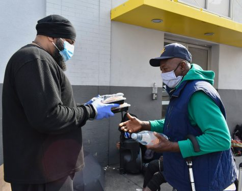 """""""The Good Karma"""" volunteer __ serves a meal to a grateful man on skid row. The charity served 300 meals on Feb. 10."""