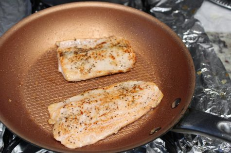 Two Alaska sockeye salmon filets cooking on a medium non-stick pan. Seasoned and heating up on one side of the fish for three minutes. Feb. 6, 2021