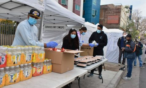 """Volunteers of """"The Good Karma"""" set up 300 meals on the corner of E 5th and San Pedro St. in Los Angeles as a line forms. As of Feb. 10, the charity has served 11,500 meals to the unhoused."""