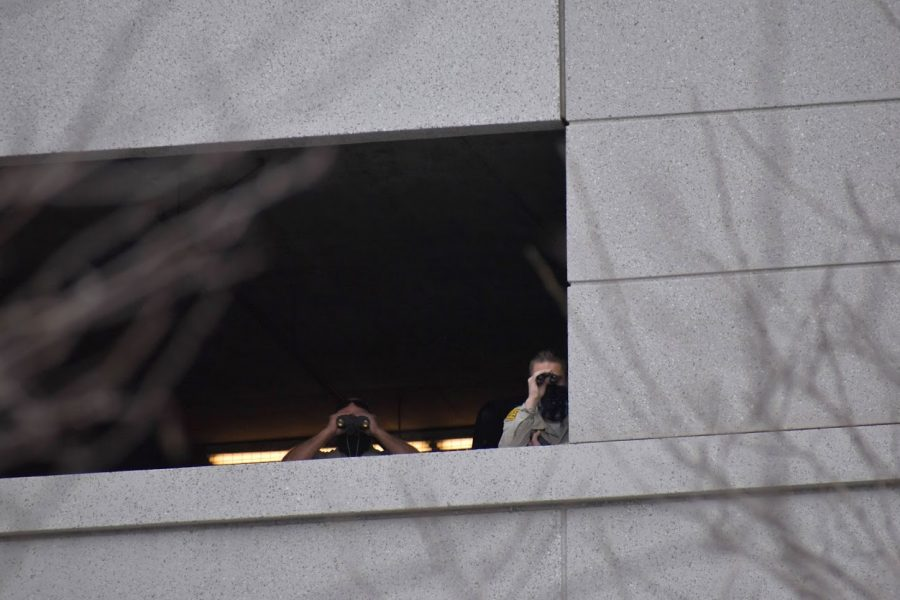 Two officers watch a peaceful Womens Day protest from a parking structure on March 8, 2021. LAPD continued to follow the demonstrators as they marched down Spring Street, leading to a stand-off in front of the Ronald Regan State Building.