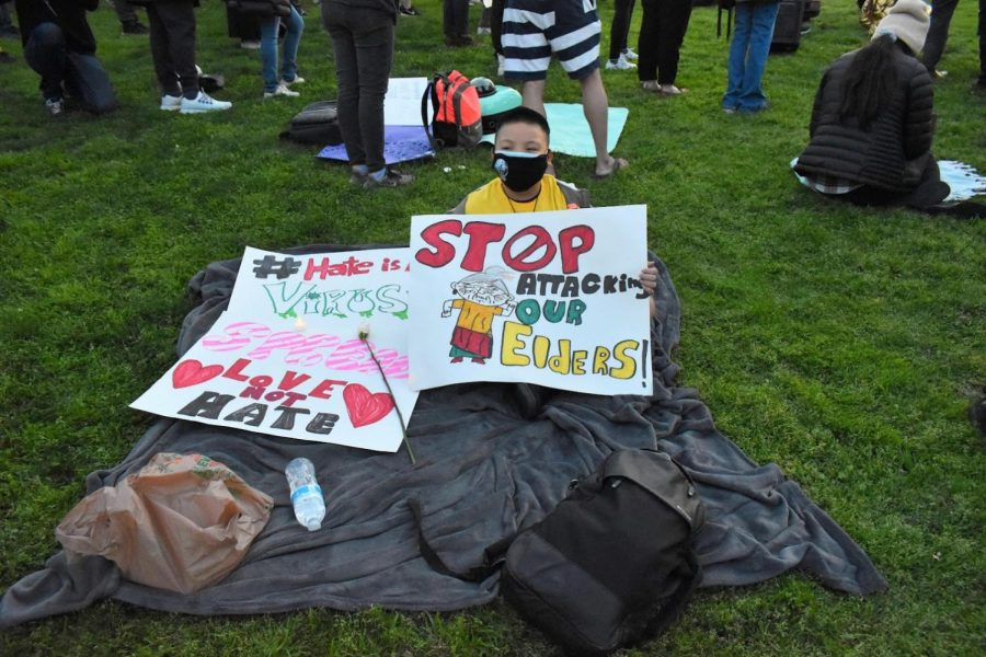 A young boy holds signs advocating for peace during a vigil in Alhambra on March 20, 2021. His signs call for an end to Asian-hate crimes and to protect elders from abuse.