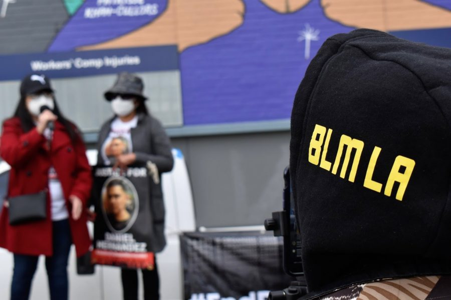 A BLM supporter listens to Maria Hernandez speak about her brother Daniel during a protest on March 8, 2021.  Maria joins the movement to bring the officers responsible to justice.