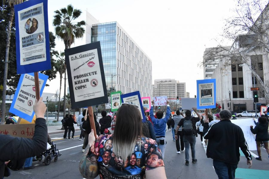 Demonstrators march down Spring Street to the Ronald Regan State Building during a Womens Day protest on March 8, 2021. They called for District Attorney Gascon to prosecute the officers responsible for murdering their loved ones.
