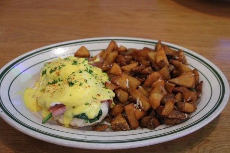Waitress sets down Luis', eggs benedicts with a side of crispy potatoes on Feb 20.