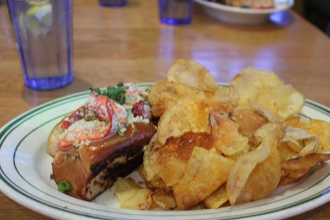 Waitress sets down Toby's mama's lobsta roll on Feb 20. A roll filled with fresh lobster with a side of house-made chips.