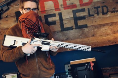 Jack Brandhorst, owner of Red Rifle arms in Carson, posing with an AR-15 on March 24. This gun is ready to picked up buy a purchaser. Photo credit: Lola Ajetunmobi