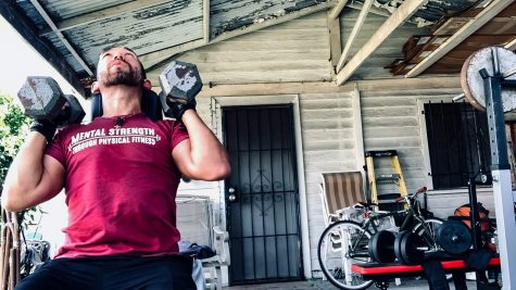 Rincon works out on Mar. 12 at his home gym. His shirt represents his belief that physical fitness can help with mental health and strength.