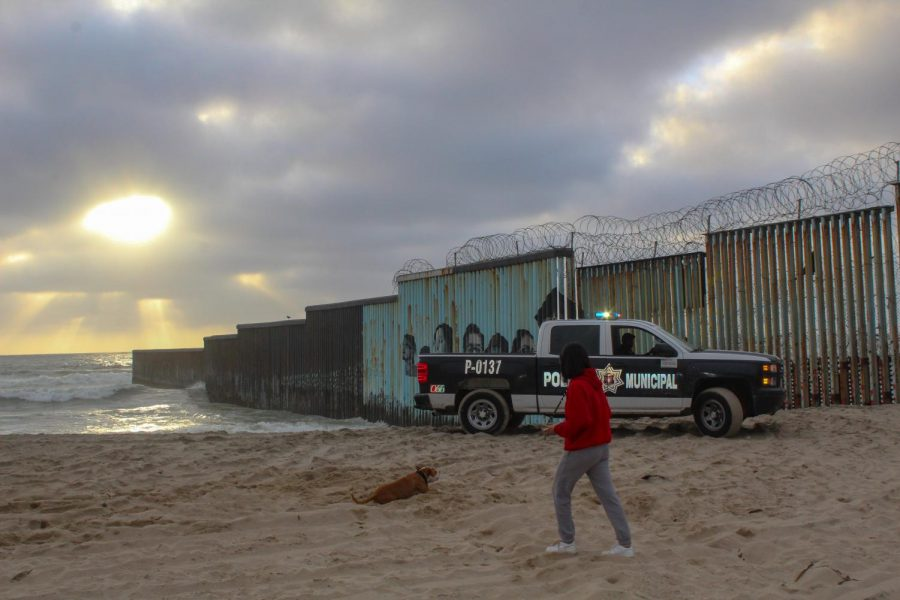 A young woman playing with her dog is kicked out of the beach by the Policía Municipal de Tijuana (Municipal Police of Tijuana) on April 10, 2021. The police's presence is constant and deter anyone from getting too close to the border wall.