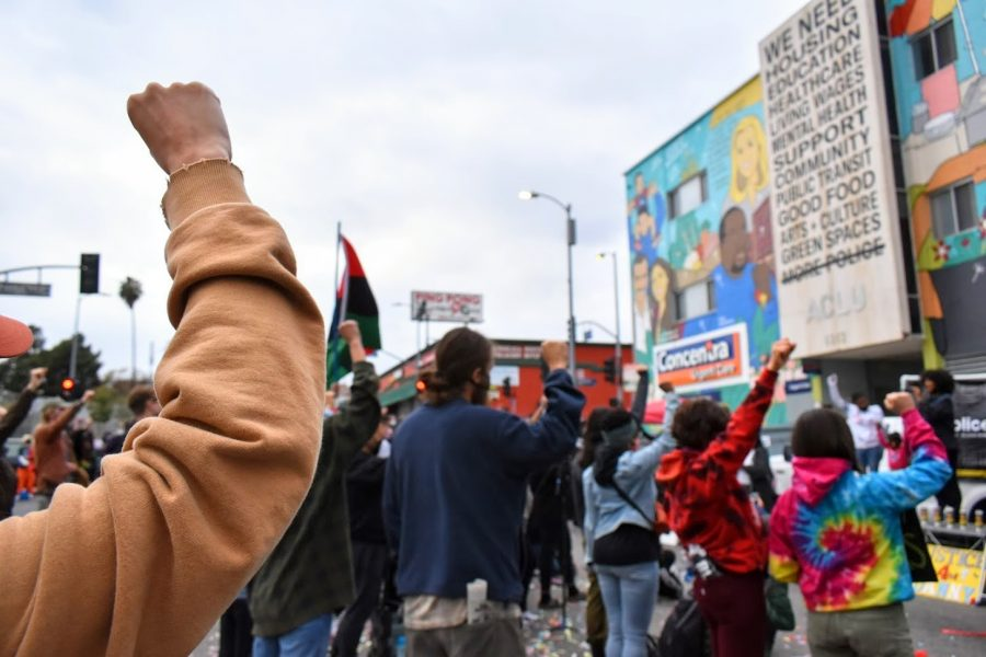Supporter of Black Lives Matter raises their fists in solidarity as the demonstration ends on April 21, 2021. They call for an end to police associations and for the LA Police Protective League to be removed from the house of labor.