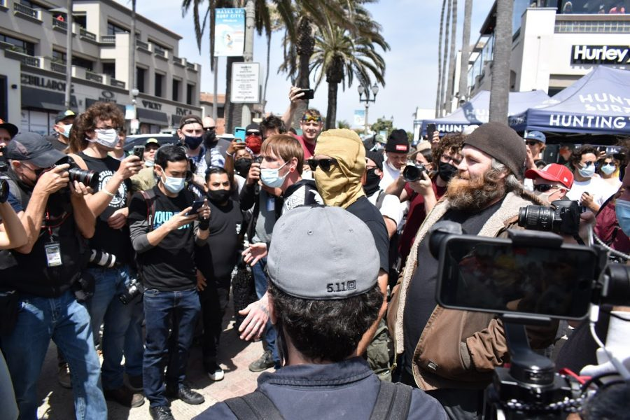 A hooded white supremacist argues with the anti-racist counter-protesters at the Huntington Beach Pier. Police escorted the man to safety at their substation on April 11, 2021.