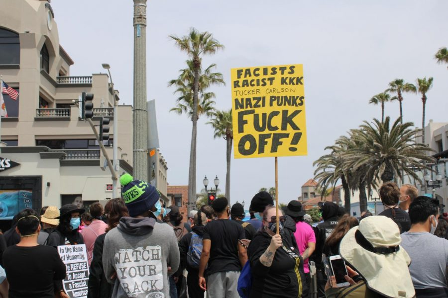 Anti-racism counter-protesters arrive to prevent a KKK protest at Huntington Beach Pier. Many protesters waved signs with strong messages against white supremacists on April 11, 2021.