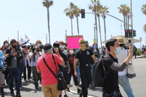 A right-wing agitator is pursued by a crowd at the Huntington Beach Pier. The man was chased until he was escorted by police into a substation on April 11, 2021. Photo credit: Lola Ajetunmobi