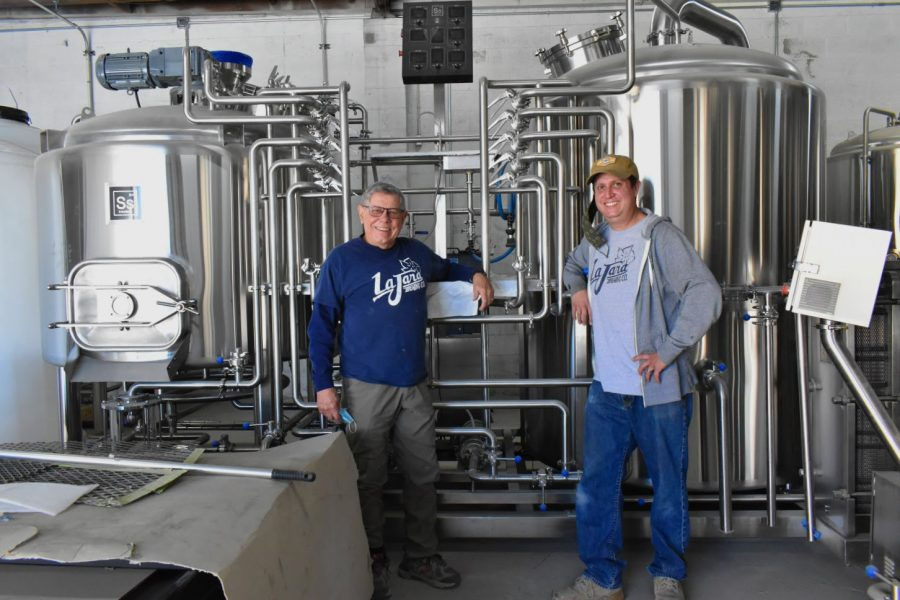 La Jara Brewing Company co-owners Randolph  (left) and Derek Johnston (right) stand with their brewing equipment. They plan to open their brewery and bar sometime in 2021.