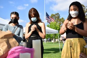 Juliana Silva (left), Laurane Garrido (middle) and Rachel Huh (right) hold a candlelight vigil for the victims of AAPI hate crimes. They hold their vigil and rally on April 24, 2021.