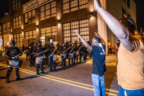 A demonstrator protesting the police killing of Andrew Brown Jr. raise their hands in front of a police line Tuesday, April 27, 2021, in downtown Elizabeth City. At least six protesters were arrested when police in riot gear marched toward roughly a dozen protesters two hours past curfew. Protesters were peaceful but refused to clear the streets.