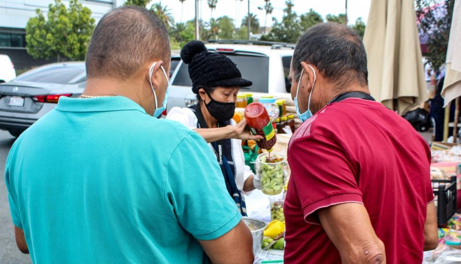 On April 25, 2021, shoppers and vendors at the El Salvador Community Corridor continue to practice social distancing and wear face masks. Vendors sell a wide range of food and goods, including various types of Central American fruit.
