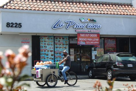A street vendor rides in front of popular Salvadoran restaurant, La Praviana. The South Gate restaurant, 8223 Long Beach Blvd, is known for 12 different pupusa recipes.